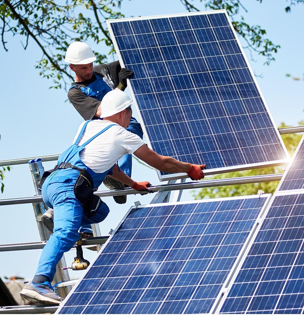 Pracownik montuje panele fotowoltaiczne na dachu
